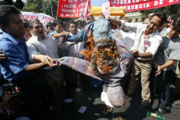 Peruvian teachers protest against President Alejandro Toledo, burning a dummy depicting the Education Minister Nicolas Lynch in front of the Congress building in Lima on Tuesday, May 14, 2002. Several unions and regional civic groups called a day of national protest and strikes against the government, the first under President Alejandro Toledo's nine-month government. Marches in Lima began peacefully, while traffic flowed freely and there were no major disturbances in the capital. (AP Photo/Silvia Izquierdo)