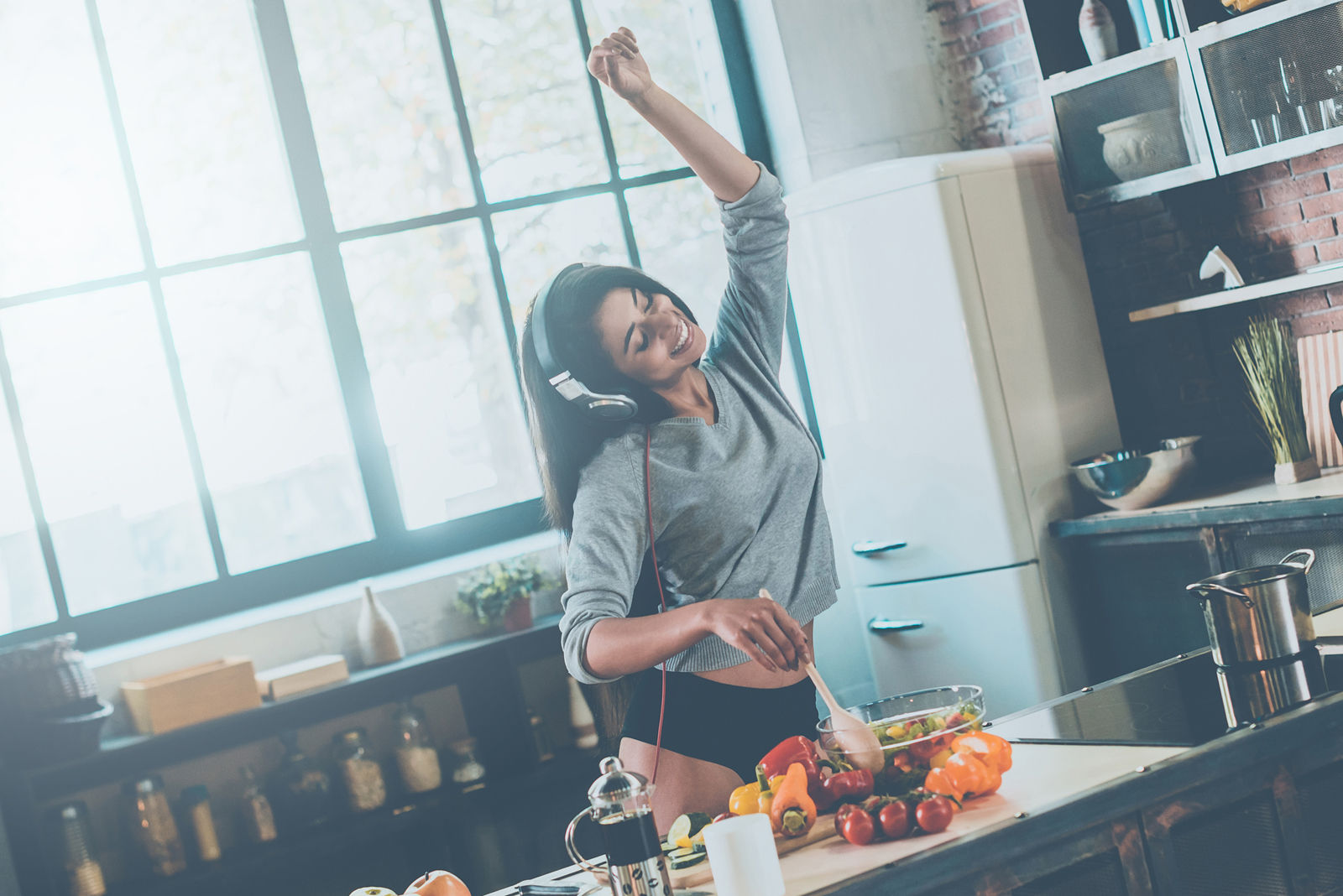 Beautiful young mixed race woman in headphones cooking salad and dancing while standing in kitchen at home