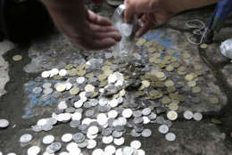 """Filipino Muslims collect coins to raise funds as docketing fee for their petition before the Supreme Court in Manila, Philippine,s Monday Sept. 24, 2012 to ban from YouTube the American-produced film """"Innocence of Muslims,"""" that ridicules Islam's Prophet Muhammad, in the Philippines. The low-budget film has angered Muslims in most parts of the world with protests turning violent and resulting in the deaths to dozens of people. (AP Photo/Bullit Marquez)"""