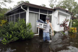 Grady Howell, of Plant City, Fla., helps a friend salvage items from a flooded mobile home Monday, Sept. 11, 2017, after Hurricane Irma moved through the area in Lakeland, Fla. (AP Photo/Chris O'Meara)