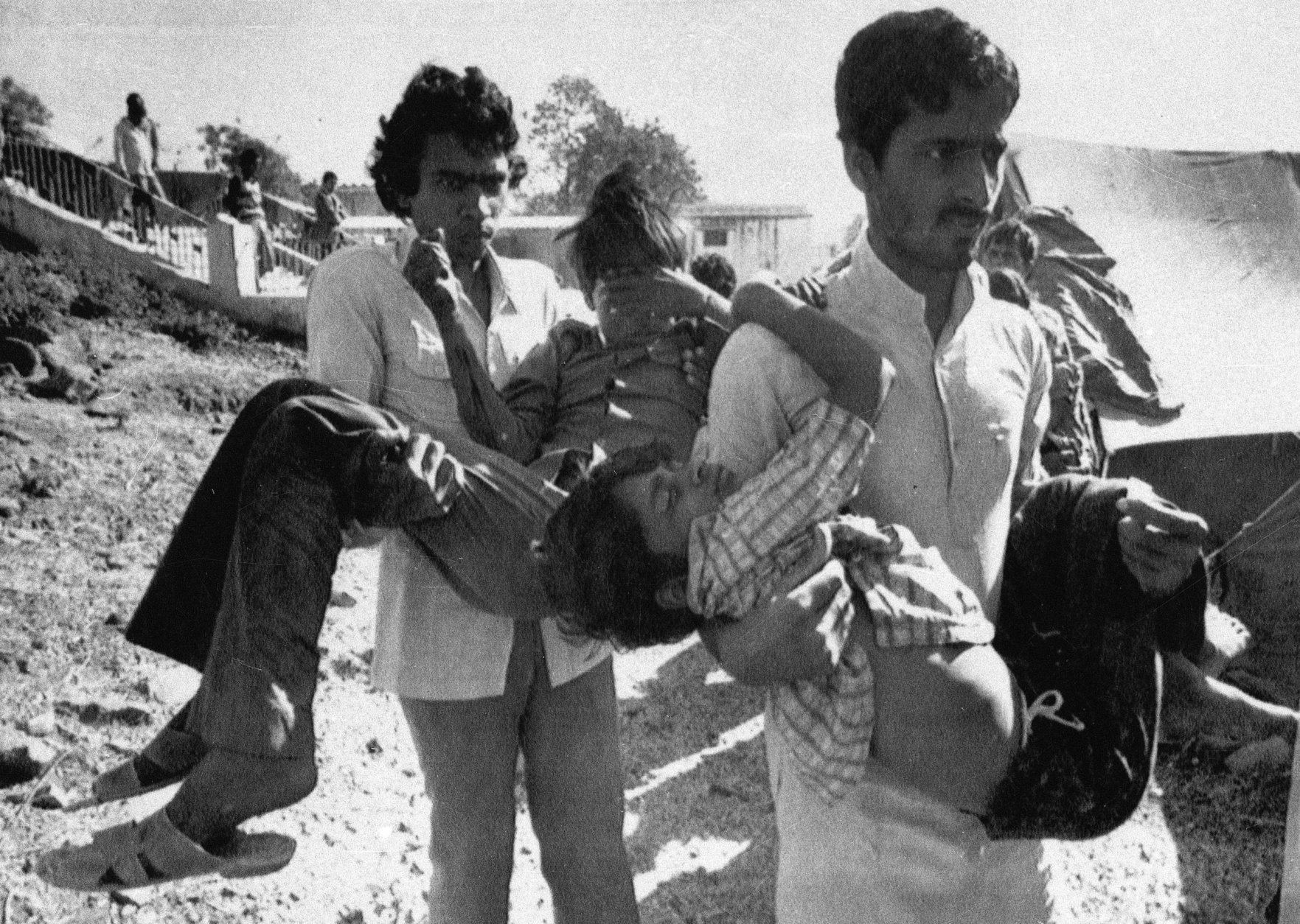 FILE – In this Dec. 5, 1984 file photo, two men carry to a hospital children blinded by the Union Carbide chemical pesticide leak in Bhopal, India. Indians are marking the 30th anniversary of the Bhopal gas leak tragedy with protests demanding harsher punishments for those responsible and more compensation for the victims of the world's worst industrial disaster. On Dec. 3, 1984, the pesticide plant leaked about 40 tons of deadly methyl isocyanate gas into the air, killing an estimated 15,000 people and affecting at least 500,000 more. Michigan-based Dow Chemical Co. took over Union Carbide in 2001. (AP Photo/Sondeep Shankar, File)