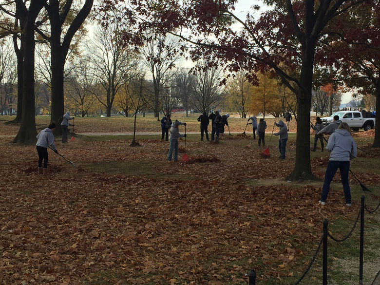 Some volunteers raked leaves near the memorial. (WTOP/John Domen)