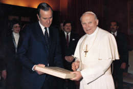 Pope John Paul II hands U.S. Vice President George Bush a book during their meeting in Vatican City, Feb. 15, 1984.   In 1984, the United States and the Vatican established full diplomatic relations for the first time in more than a century. (AP Photo/Arturo Mari)