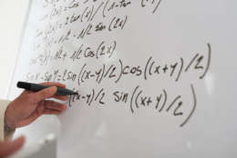 Close-up image of male hand writing math equations on the board