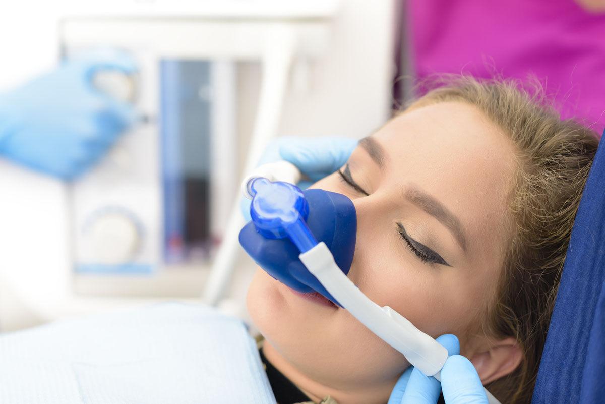 Beautiful getting woman inhalation sedation at dental clinic