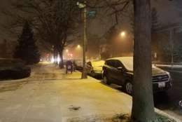 Snow accumulates on cars along Wisconsin Ave. in Northwest D.C. (WTOP/William Vitka)