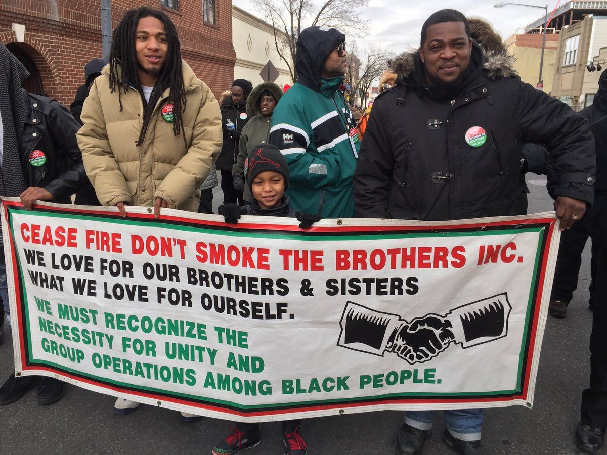 Event-goers hold up a sign at the MLK Peace Walk and Parade. (WTOP/Kristi King)