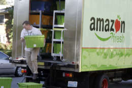 Amazon Fresh delivery man Tim Wilkie prepares a grocery order for delivery to a residence on Mercer Island, Wash., Thursday, Aug. 23, 2007. Amazon Fresh is a new grocery delivery service being tested by Amazon.com in a handful of Seattle neighborhoods including Mercer Island. Amazon.com has deployed a fleet of 12 grocery delivery trucks. Customers can also pick up fresh grocery orders at a small number of locations in the area. (AP Photo/Joe Nicholson)