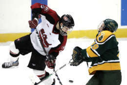 St. Cloud State center Garrett Roe (9) is checked by Clarkson winger David Cayer (19) during the second period of their NCAA East Regional semifinal hockey game in Albany, N.Y., Friday, March 28, 2008.  (AP Photo/Mike Groll)