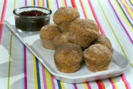 In this May 23, 2016 photo, doughnut puffs with dark chocolate dipping sauce, styled by Sarah Abrams, are displayed at the Institute of Culinary Education in New York. The puffs, which look like a mini muffin coated in cinnamon sugar, were created by Elizabeth Karmel based on her memory of a favorite sweet she and her sister used to enjoy in a New York bakery. (AP Photo/Richard Drew)