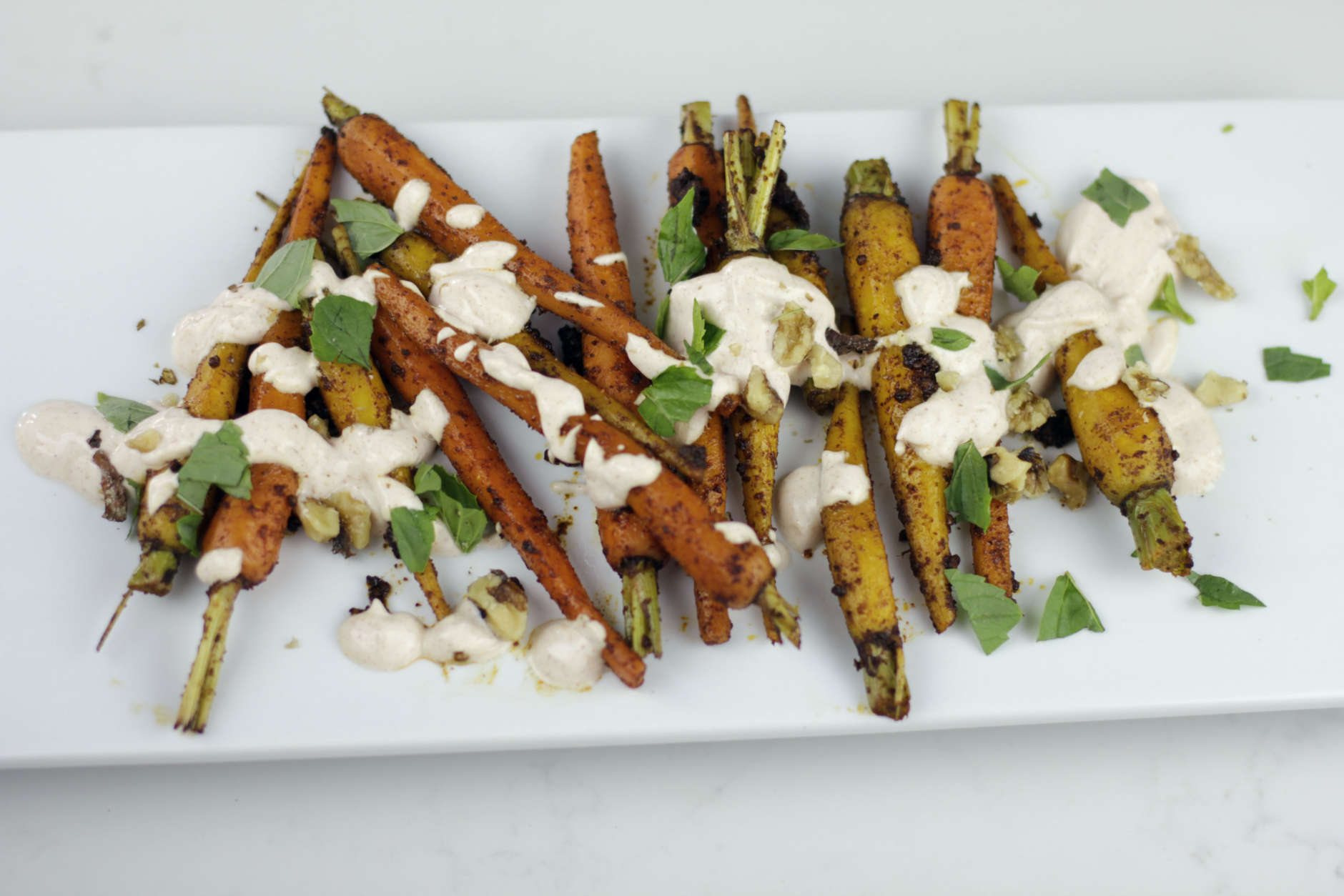 This July 12, 2016 photo shows Moroccan spiced carrots with yogurt sauce in Coronado, Calif. This dish is from a recipe by Melissa d'Arabian. (Melissa d'Arabian via AP)