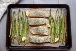 This Jan. 2, 2017 photo shows a sheet-pan supper of salmon and asparagus in Coronado, Calif., a recipe by Melissa d'Arabian. (Melissa d'Arabian via AP)