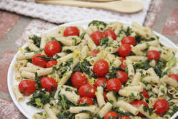 This April 2017 photo shows penne with tomatoes, garlic, lemon and spinach in Coronado, Calif. This dish is from a recipe by Melissa d'Arabian. (Melissa d'Arabian via AP)
