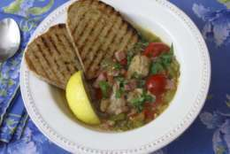 Thie June 20, 2017 photo shows a clam, tomato and bacon stew with grilled garlic bread in New York. This dish is from a recipe by Sara Moulton. (Sara Moulton via AP)