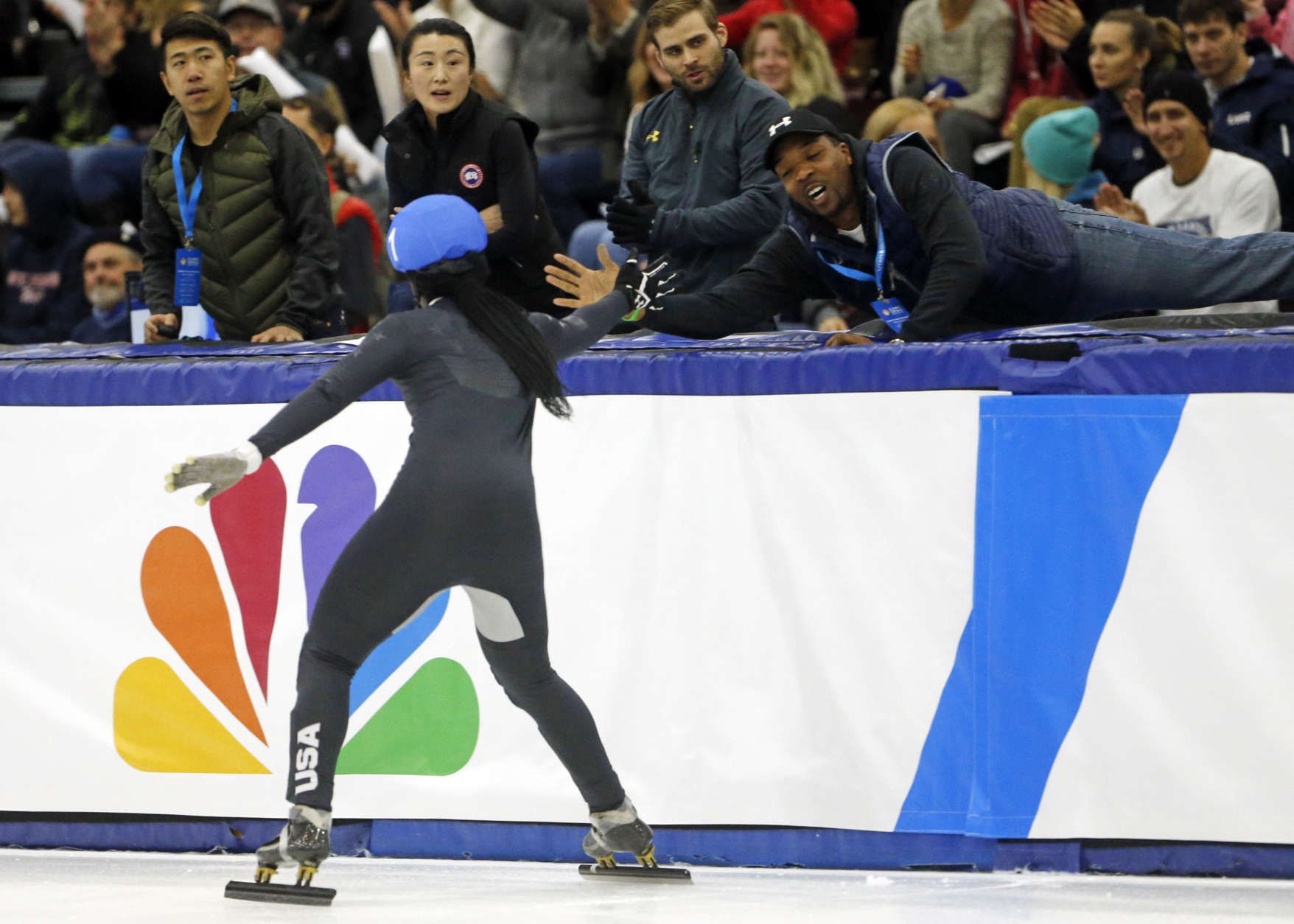 Maame Biney (1) celebrates with her coach after winning the women's 500-meter final A during the U.S .Olympic short track speedskating trials Saturday, Dec. 16, 2017, in Kearns, Utah. (AP Photo/Rick Bowmer)