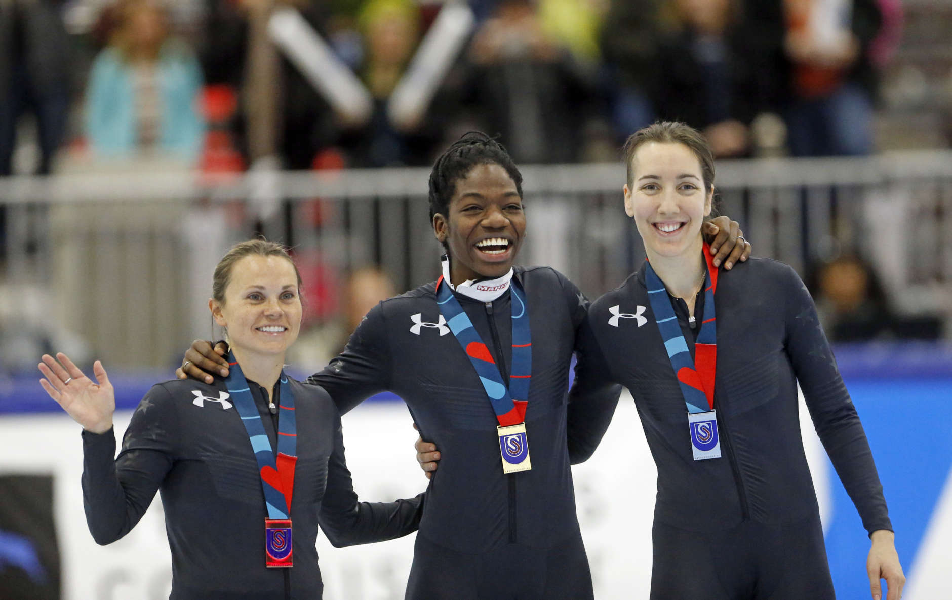 First place finisher Maame Biney, center, stands with third place finisher Jessica Kooreman, left, and second place finisher Lana Gehring, right, following the women's 500-meter during the U.S. Olympic short track speedskating trials Saturday, Dec. 16, 2017, in Kearns, Utah. (AP Photo/Rick Bowmer)