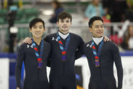 First place finisher John-Henry Krueger, center, stands with third place finisher, left, Thomas Insuk Hong and second place finisher Aaron Tran, right, following the men's 500-meter during the U.S. Olympic short track speedskating trials Saturday, Dec. 16, 2017, in Kearns, Utah. (AP Photo/Rick Bowmer)