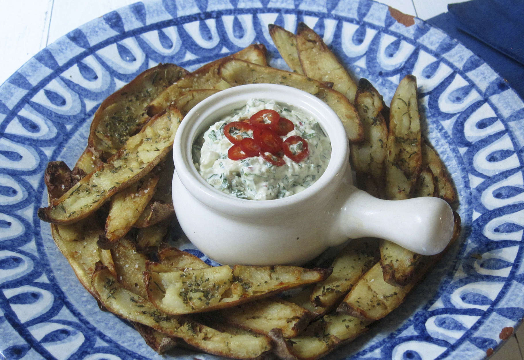 """This Jan. 9 2018 photo shows potato skins baked with roasted garlic rosemary butter and an onion kale dip spiked with fresh chiles. This dish is from the recipe """"Decadent Snacks for the Super Bowl"""" by Sara Moulton. (Sara Moulton via AP)"""