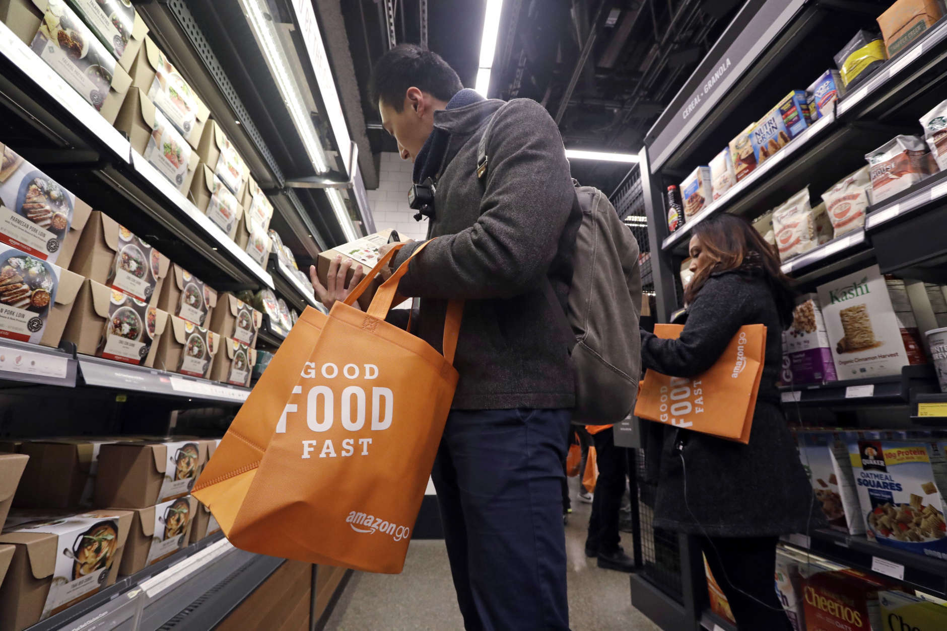 Customer Paul Fan shops at an Amazon Go store, Monday, Jan. 22, 2018, in Seattle. The store on the bottom floor of the company's Seattle headquarters allows shoppers to scan their smartphone with the Amazon Go app at a turnstile, pick out the items they want and leave. The online retail giant can tell what people have purchased and automatically charges their Amazon account. (AP Photo/Elaine Thompson)