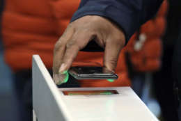 A shopper scans an Amazon Go app on a cellphone while entering an Amazon Go store, Monday, Jan. 22, 2018, in Seattle. The artificial intelligence-powered store, which opened to the public on Monday, allows shoppers to scan their smartphone with the Amazon Go app at a turnstile, pick out the items they want and leave. The online retail giant can tell what people have purchased and automatically charges their Amazon account. (AP Photo/Elaine Thompson)