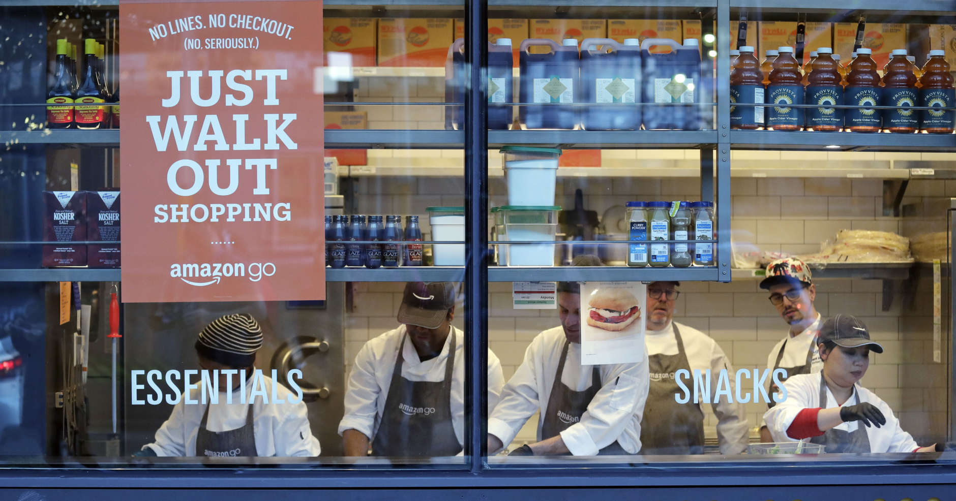 Workers as seen from a sidewalk window as they assemble sandwiches in an Amazon Go store Monday, Jan. 22, 2018, in Seattle. More than a year after it introduced the concept, Amazon opened its artificial intelligence-powered Amazon Go store in downtown Seattle on Monday. The store on the bottom floor of the company's Seattle headquarters allows shoppers to scan their smartphone with the Amazon Go app at a turnstile, pick out the items they want and leave. (AP Photo/Elaine Thompson)
