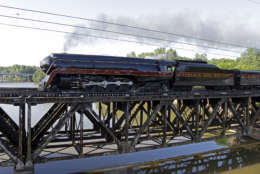 The Norfolk & Western Class J No. 611 steam locomotive crosses a bridge over the Yadkin River after leaving the North Carolina Transportation Museum in Spencer, N.C., Saturday, May 30, 2015. The train, which has undergone a year-long restoration, is returning to the Virginia Museum of Transportation in Roanoke, Virginia. (AP Photo/Chuck Burton)