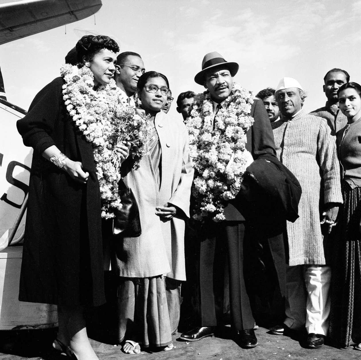"American civil rights leader Rev. Dr. Martin Luther King, Jr. and his wife Coretta, both wearing garlands, are received by admirers after landing at the airport in New Delhi, India, Feb. 10, 1959.  King, who is known here as the American Gandhi, flew here on what he calls a ""four-week pilgrimage in India which to me means Mahatma Gandhi.""  (AP Photo/R. Satakopan)"