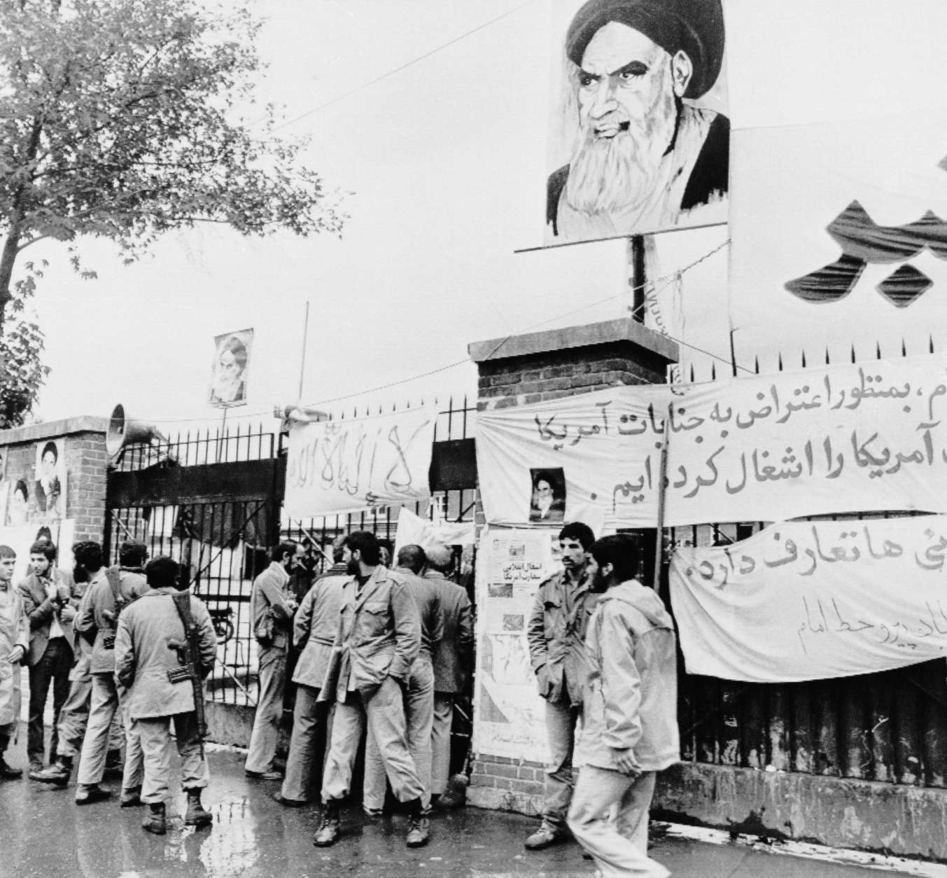 FILE - In this Nov. 6, 1979 file photo, students stand guard before the entrance of the United States Embassy where staff is being held hostage in Tehran, as a portrait of Ayatollah Khomeini is on display. The Obama administration asked a federal judge Tuesday, April 21, 2009 to throw out a lawsuit against Iran filed by Americans held hostage at the embassy in Tehran 30 years ago. In court papers filed Tuesday night, the Justice Department argued that the agreement to release the hostages precluded lawsuits against Iran. (AP Photo/File)
