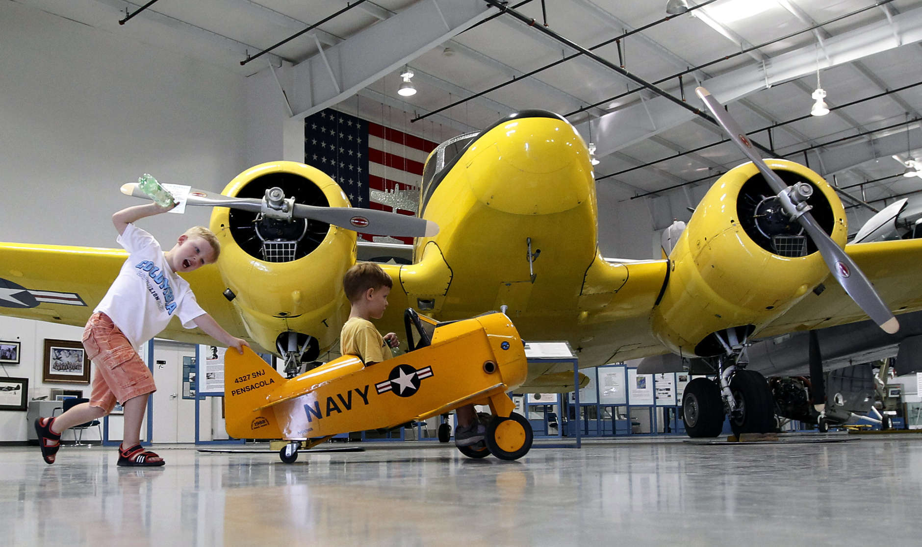 "Two youngsters enjoy riding around in a toy plane as they ride in front of a Cessna T-50 ""Bobcat"" transport trainer plane, from 1939-1949, at the Commemorative Air Force Aviation Museum Thursday, Aug. 2, 2012, in Mesa, Ariz.(AP Photo/Ross D. Franklin)"