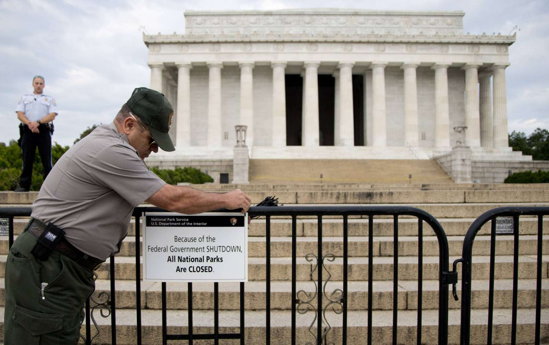 FILE - In this Oct. 1, 2013, file photo, A U.S. Park Police officer watches at left as a National Park Service employee posts a sign on a barricade closing access to the Lincoln Memorial in Washington. (AP Photo/Carolyn Kaster, File)