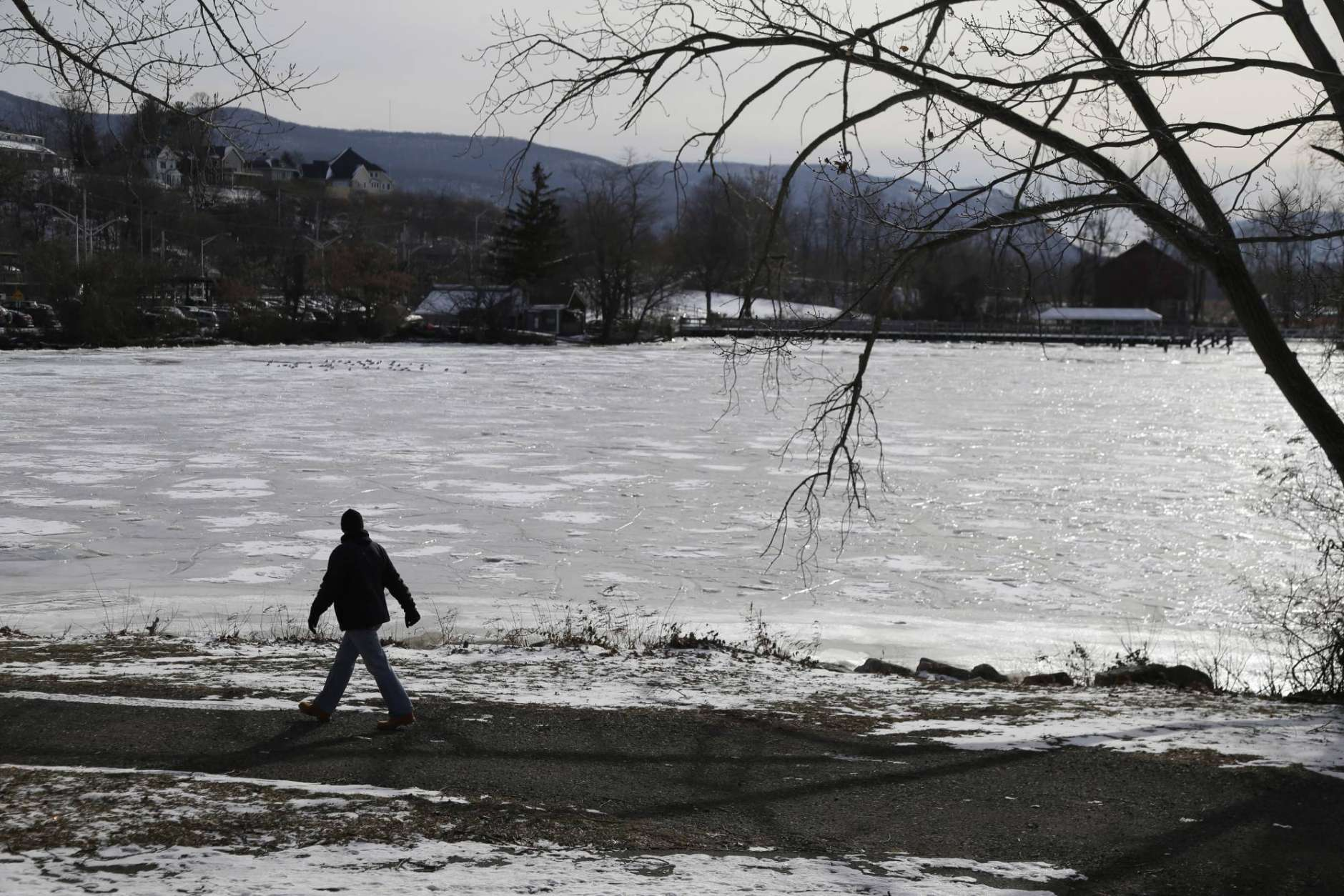 A man walks past a frozen part of the Hudson River in Beacon, N.Y., Wednesday, Jan. 3, 2018. Bitterly cold temperatures gripped much of the nation on Tuesday, testing the mettle of even winter-wise northerners and delivering a shock to those accustomed to far milder weather in the South. (AP Photo/Seth Wenig)