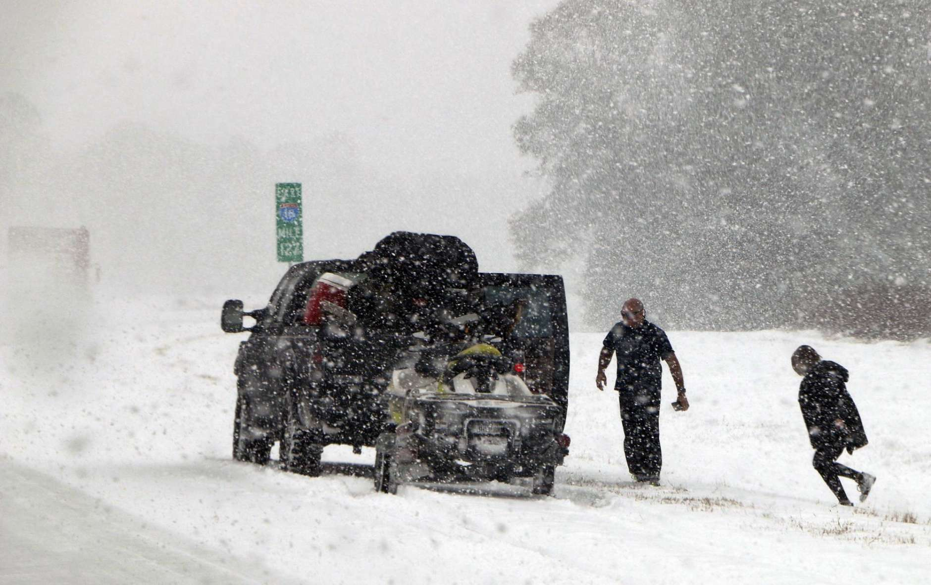 People attend to their vehicle on Interstate 26, near Savannah, Ga., Wednesday, Jan. 3, 2018. A brutal winter storm dumped snow in Tallahassee, Fla., on Wednesday for the first time in nearly three decades before slogging up the Atlantic coast and smacking Southern cities such as Savannah and Charleston, South Carolina, with a rare blast of snow and ice. (AP Photo/Robert Ray)