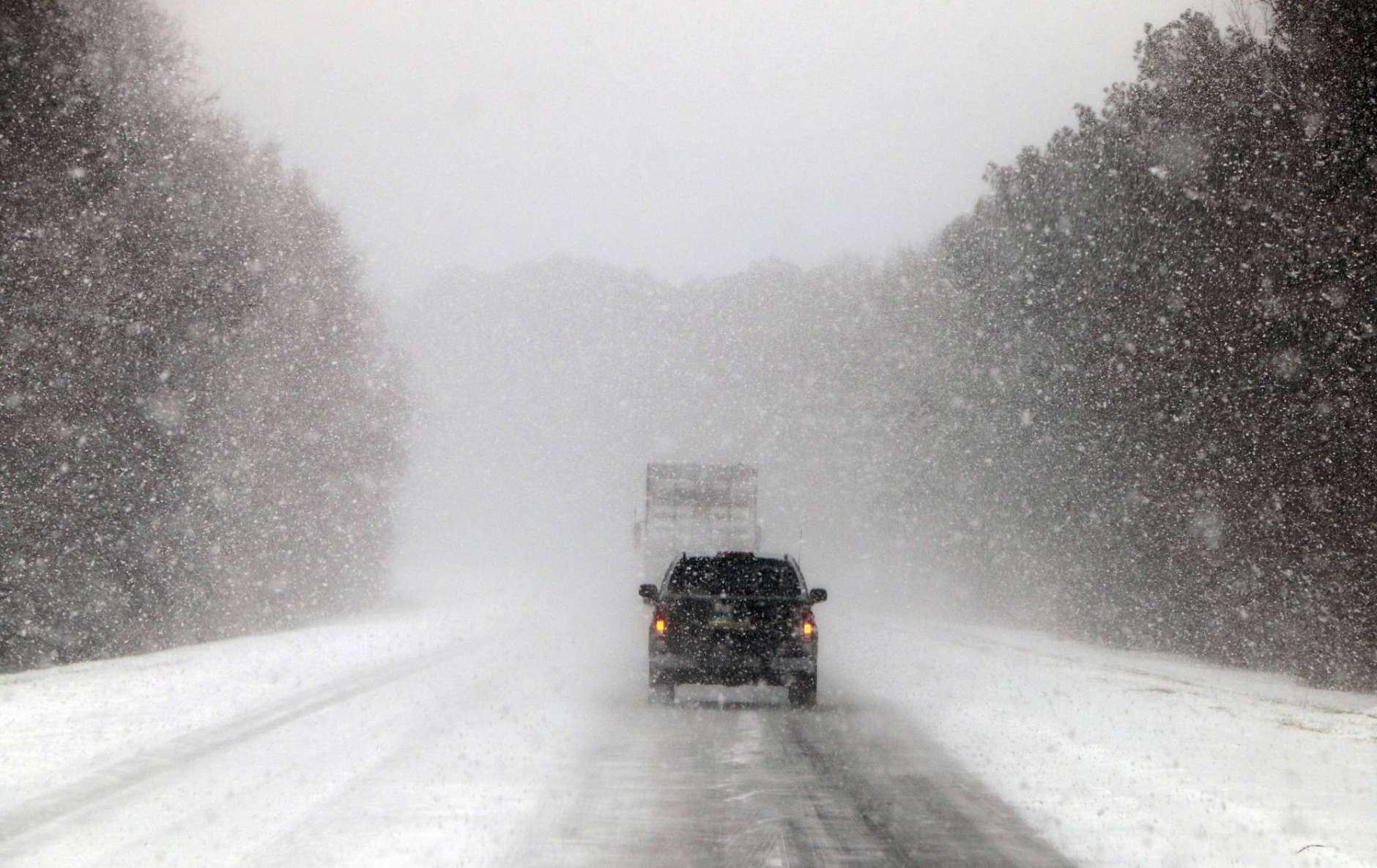 Vehicles move along a snow and ice covered Interstate 26, near Savannah, Ga., Wednesday, Jan. 3, 2018. A brutal winter storm dumped snow in Tallahassee, Fla., on Wednesday for the first time in nearly three decades before slogging up the Atlantic coast and smacking Southern cities such as Savannah and Charleston, South Carolina, with a rare blast of snow and ice. (AP Photo/Robert Ray)