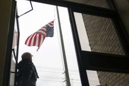 A United States Postal Worker takes down a frozen American flag after the top hook that attached it to the pole broke and caused the flag to fly upside down, Wednesday, Jan. 3, 2018, in Savannah, Ga.  A brutal winter storm scattered a wintry mix of snow, sleet and freezing rain from normally balmy Florida up the Southeast seaboard Wednesday. (AP Photo/Stephen B. Morton)