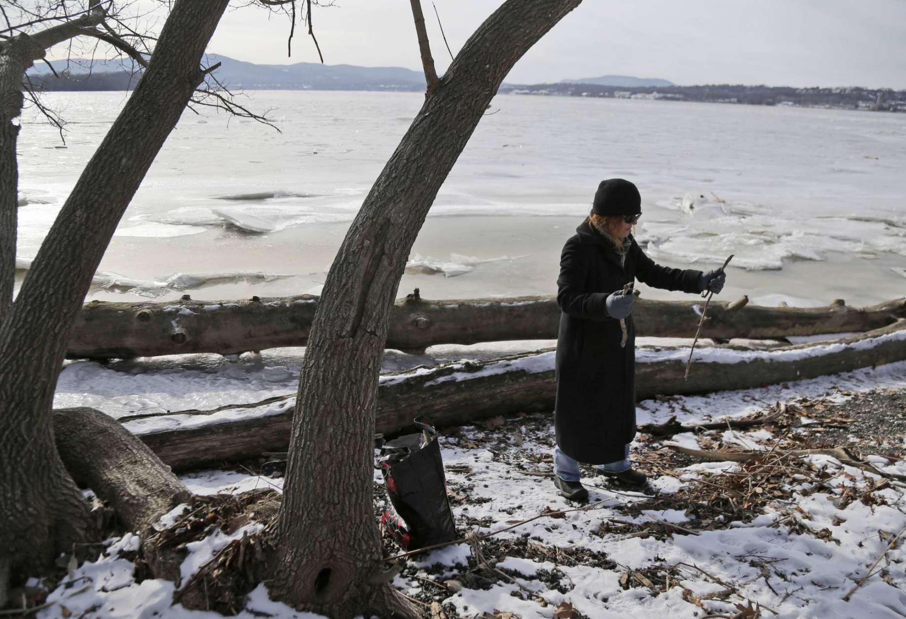 Valerie Hinkle collects kindling along the edge of the partially frozen Hudson River in Beacon, N.Y., Wednesday, Jan. 3, 2018. Hinkle was concerned that in incoming storm might knock out the power and she wanted to able to build a fire. Bitterly cold temperatures gripped much of the nation on Tuesday, testing the mettle of even winter-wise northerners and delivering a shock to those accustomed to far milder weather in the South. (AP Photo/Seth Wenig)