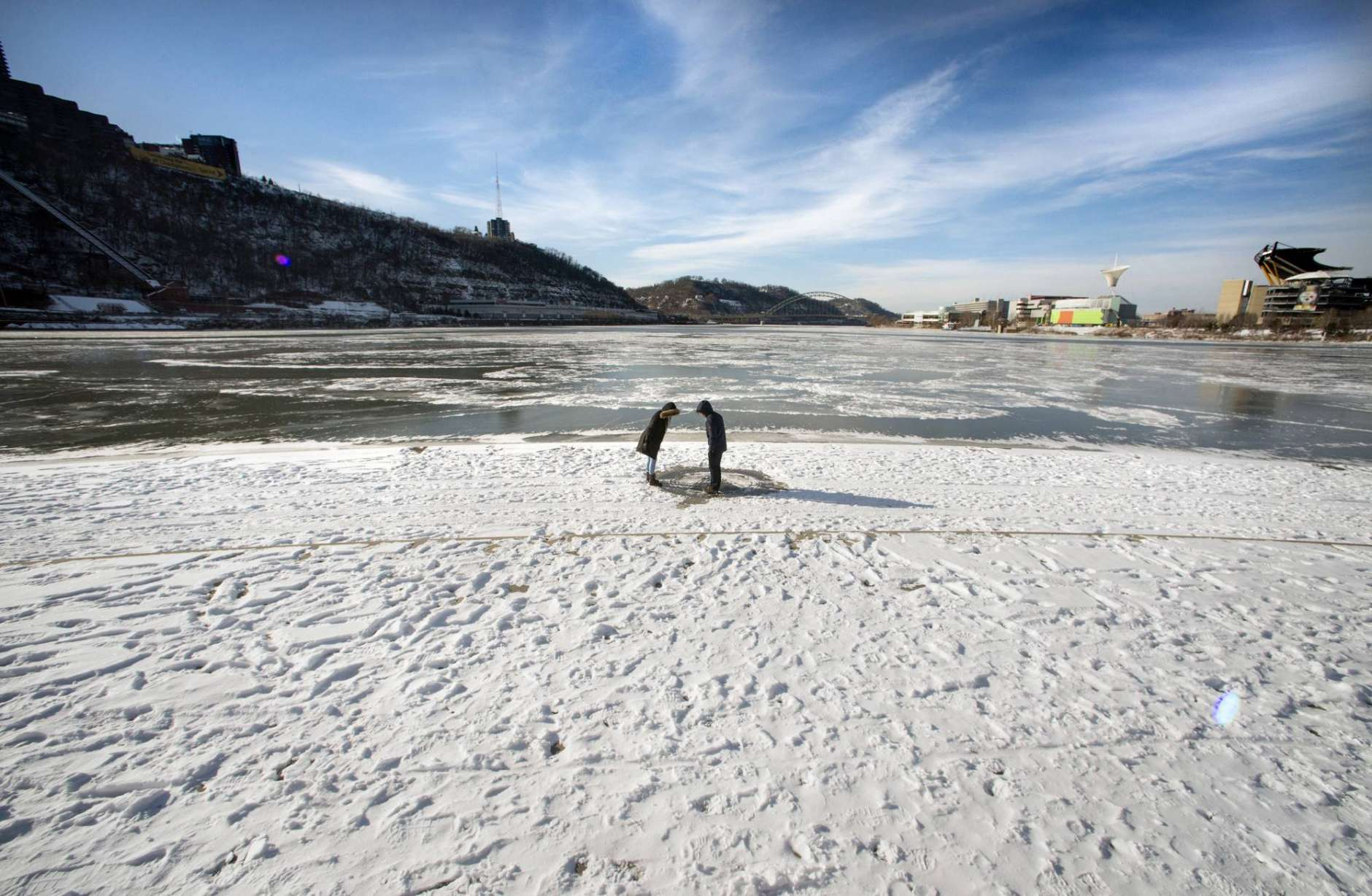 Samantha Ritter of Robinson gave Matthew Sun his first glimpse of Pittsburgh's Point, which was snow-covered and frozen on Tuesday, Jan. 2, 2018. Sun is from Sterling, Va., near Washington DC.(Steve Mellon/Post-Gazette via AP)