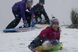 Children sled down a hill on a golf course at the Isle of Palms, S.C., Wednesday, Jan. 3, 2018. A brutal winter storm dumped snow in Tallahassee, Florida, on Wednesday for the first time in nearly three decades before slogging up the Atlantic coast and smacking Southern cities such as Savannah and Charleston, South Carolina, with a rare blast of snow and ice. (AP Photo/Mic Smith)