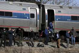 Passengers watch as emergency personnel operate work at the scene of a train crash involving a garbage truck in Crozet, Va., on Wednesday, Jan. 31, 2018. An Amtrak passenger train carrying dozens of GOP lawmakers to a Republican retreat in West Virginia struck a garbage truck south of Charlottesville, Va. No lawmakers were believed injured. (Zack Wajsgrasu/The Daily Progress via AP)