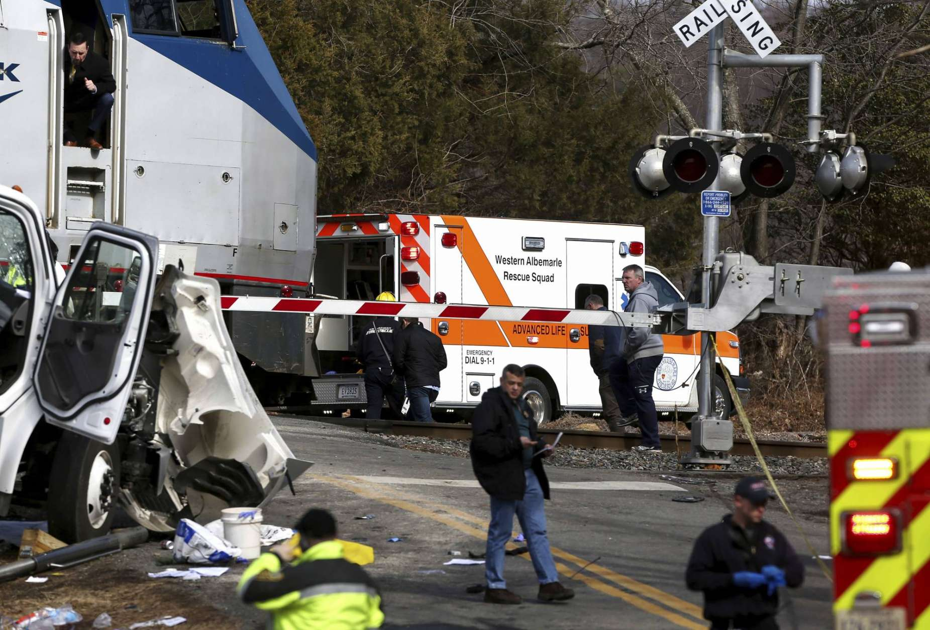 The railroad crossing arm is seen lowered next to the scene of where an Amtrak train carrying multiple Republican lawmakers crashed into a garbage truck  in Crozet, Va., on Wednesday, Jan. 31, 2018.  A chartered train carrying dozens of GOP lawmakers to a Republican policy retreat in West Virginia struck a garbage truck in a rural Virginia town Wednesday.  (Zack Wajsgras/The Daily Progress via AP)