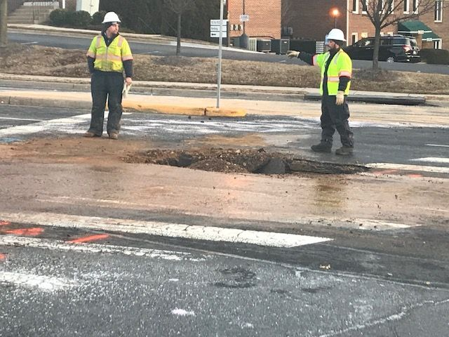 Utility crews work on a broken water main in Fairfax. (WTOP/Michael O'Connell)