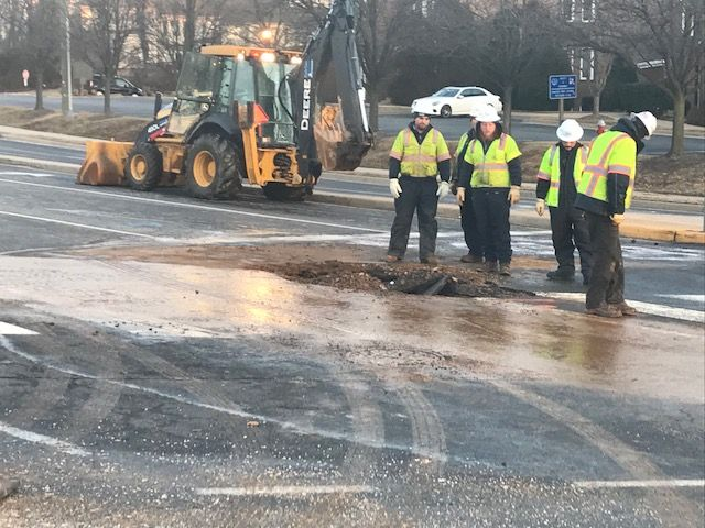 Utility crews work on repairing a broken water main Wednesday morning in Fairfax County. (WTOP/Michael O'Connell)