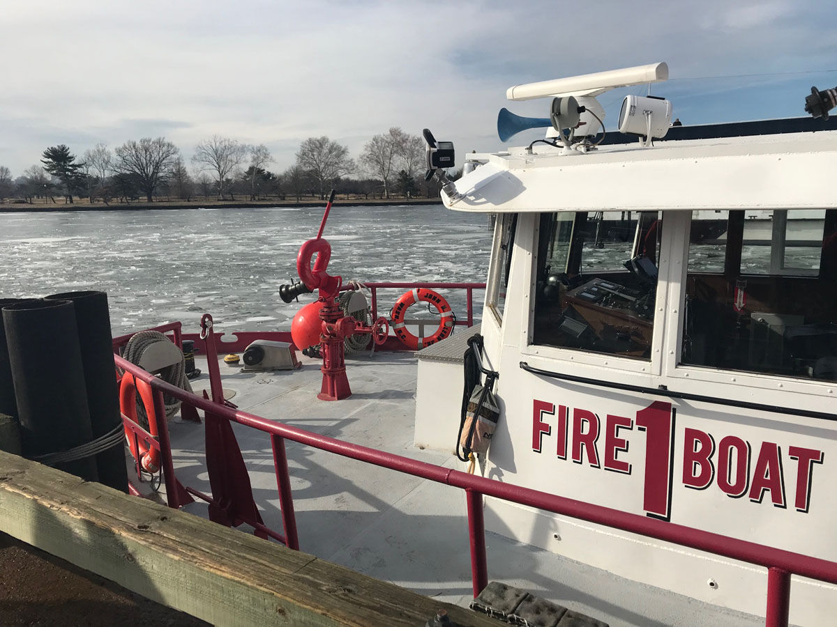 D.C. firefighters, specially trained by the U.S. Coast Guard, work to break up large ice sheets that formed in frigid temperatures blocking access on the waterway in an emergency.  (WTOP/Megan Cloherty)