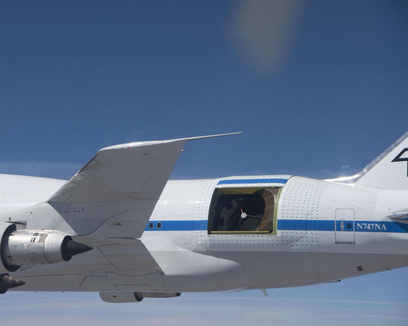 With its primary mirror covered by a protective sun shade, the German-built infrared telescope nestled in its cavity in the rear fuselage of NASA's SOFIA flying observatory is easily visible in this close-up image taken during a test flight. The small blue lines surrounding the telescope cavity are aerodynamic tufts to visibly show how air flows over the cavity in different flight attitudes. (Courtesy NASA/USRA)