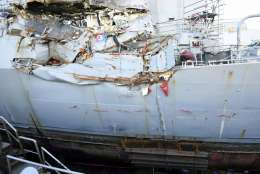 FILE - In this July 11, 2017 file photo, provided by the U.S. Navy, the USS Fitzgerald sits in dry dock in Yokosuka, Japan, to continue repairs and assess damage sustained from a June 17 collision with a cargo ship ran in the waters off of Japan. The Navy says it is filing negligent homicide charges against the commanders of two ships involved in fatal collisions last year. The charges are to be presented at what the military calls an Article 32 hearing, which will determine whether the accused are court martialed.  (Spc. 1st Class Leonard Adams/U.S. Navy via AP)