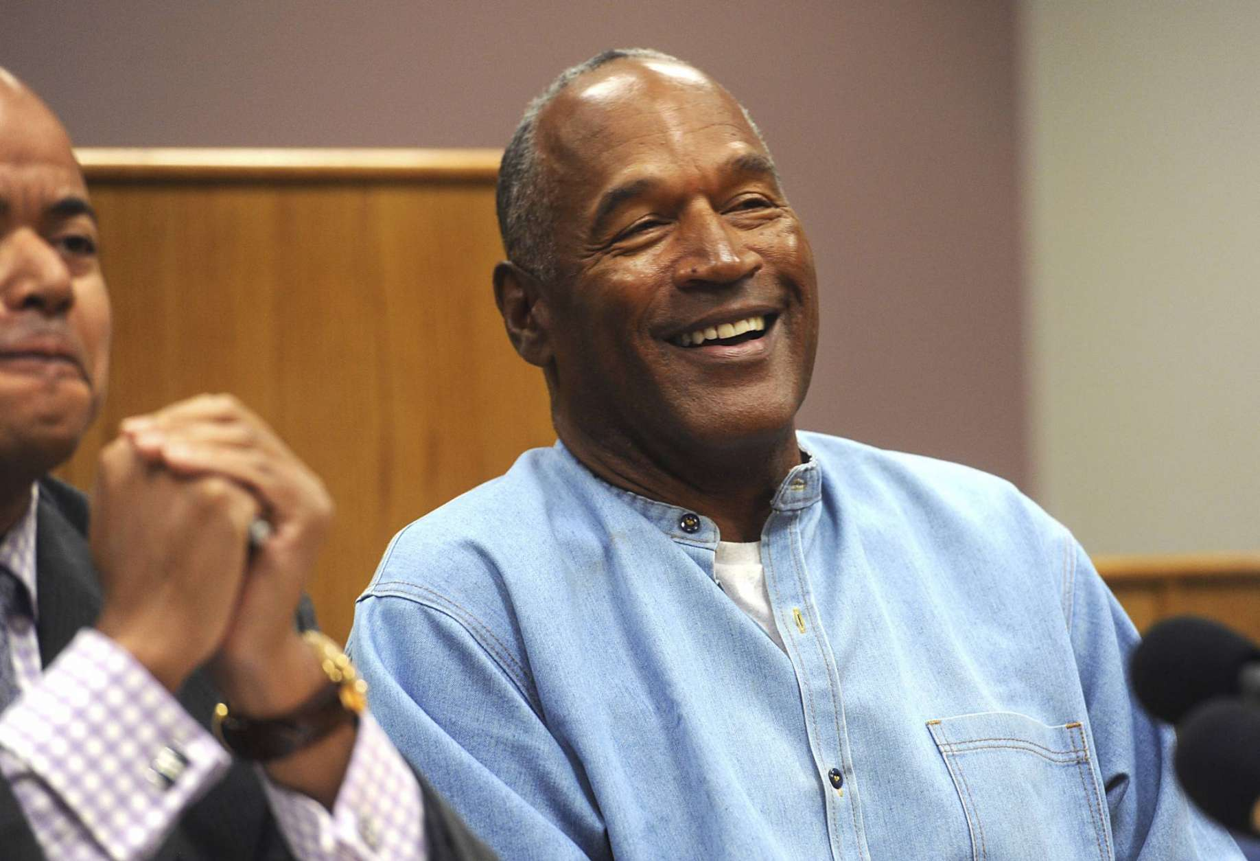 FILE - In this July 20, 2017, file photo, former NFL football star O.J. Simpson laughs as he appears via video for his parole hearing at the Lovelock Correctional Center in Lovelock, Nev. Simpson enjoys living in Las Vegas, and isn't planning to move to Florida like he told state parole officials before he was released in October from Nevada state prison. (Jason Bean/The Reno Gazette-Journal via AP, Pool, File)
