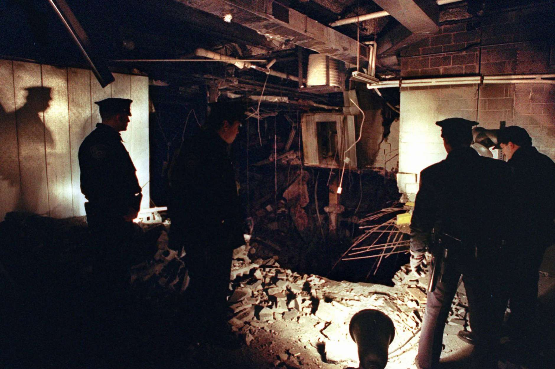 FILE-- In this Feb. 27, 1993 file photo, Port Authority and New York City Police officers view the damage caused by a truck bomb that exploded in the garage of New York's World Trade Center the previous day. The National September 11 Memorial & Museum on Friday, Jan. 26, 2018,  announced the opening of a special installation to commemorate the 25th anniversary of the 1993 truck bombing of the World Trade Center. (AP Photo/Richard Drew, File)