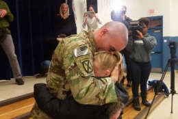 Brent Mount hugs his daughter Katie after surprising her during a school assembly Monday morning at Park Ridge Elementary in Stafford County. Mount has spent the last six months deployed to Afghanistan. (WTOP/Kathy Stewart)