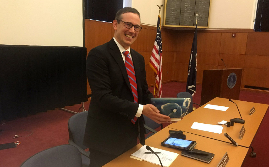 Virginia Board of Elections chairman James Alcorn shows off the blue stoneware blue used in the drawing to break a tie in the disputed 94th District House Race on Jan. 4, 2018, in Richmond, Virginia. Virginia artist Steven Glass crafted the vessel, which represents the sky on the outside of the bowl and the oxide red inside represents the earth. (WTOP/Max Smith)