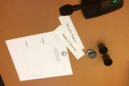 Two film canisters, which election officials said were ordered new from Amazon, and the names of the candidates printed on slips of paper await a drawing to break a tie in the 94th House race in Newport News. The drawing in Richmond declared Republican David Yancey the winner on Jan. 4, 2018 almost two months after the November election.  (WTOP/Max Smith)