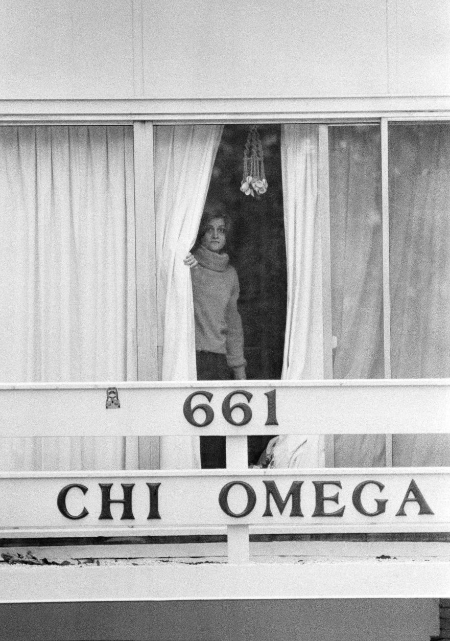 An unidentified woman peers through drapes on the 2nd story balcony of the Chi Omega sorority house at Florida State University in Tallahassee, Fla., Jan. 15, 1978. Two sorority sisters, Margaret Bowman and Lisa Levy, were brutally beaten to death with the assailant leaving 3 others injured early Sunday morning. (AP Photo/Mark Foley)